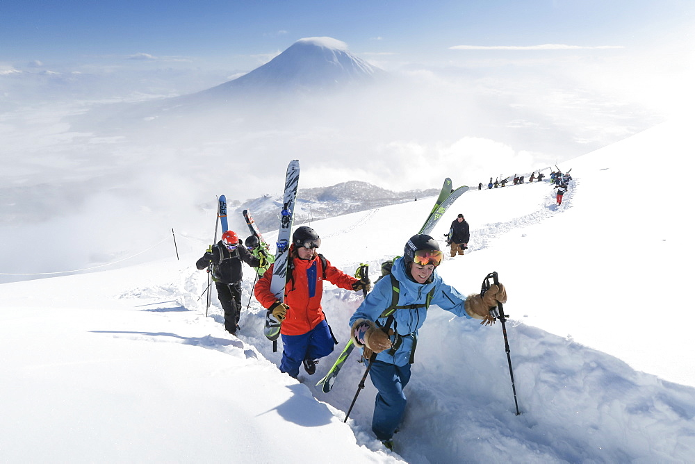 With Mount Yotei in the background, a team of backcountry skiers, led by a woman, are hiking to the summit of mount Annupuri, near ski resort Niseko United on the Japanese island of Hokkaido. The skis they carry are big and wide allowing the winter enthusiasts to fully enjoy skiing down the waist deep powder slopes Niseko United is known for. Niseko United is comprised of four resorts on the one mountain, Annupuri (1,308m). 100km south of Sapporo, Niseko Annupuri is a part of the Niseko-Shakotan-Otaru Kaigan Quasi-National Park and is the most eastern park of the Niseko Volcanic Group. Hokkaido, the north island of Japan, is geographically ideally located in the path of consistent weather systems that bring the cold air across the Sea of Japan from Siberia. This results in many of the resorts being absolutely dumped with powder that is renowned for being incredibly dry. Some of the Hokkaido ski resorts receive an amazing average of 14-18 meters of snowfall annually. Niseko is the powder capital of the world and as such is the most popular international ski destination in Japan. It offers an unforgettable experience for all levels of skier and snowboarder.