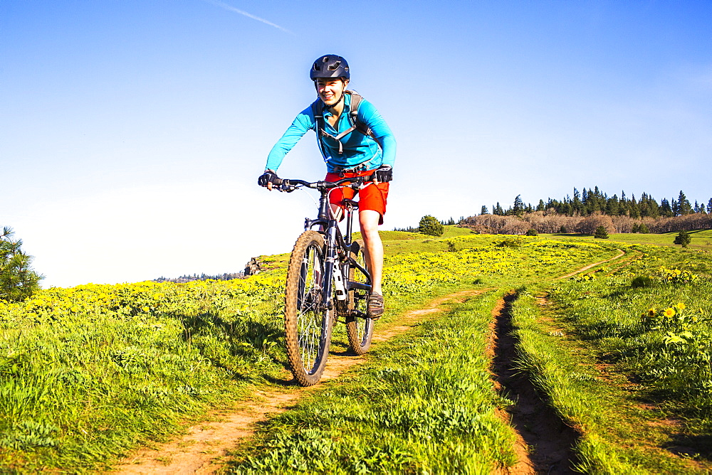 A young woman facing camera rides a mountain bikes down a single-track trail through a meadow.