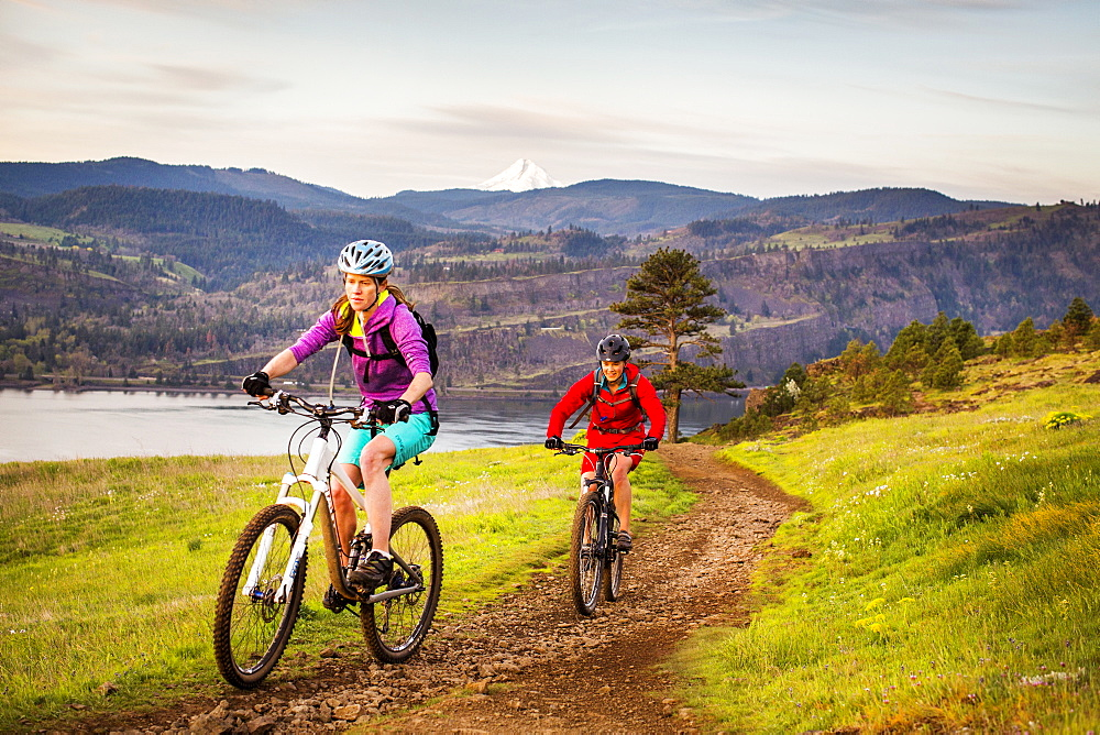 Two young women ride mountain bikes up a single-track trail with volcano in distance.