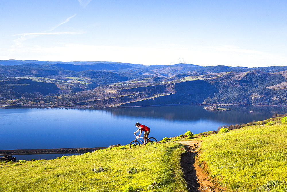 A man rides a mountain bike downhill on a single-track trail through green grass with a large river in the distance.