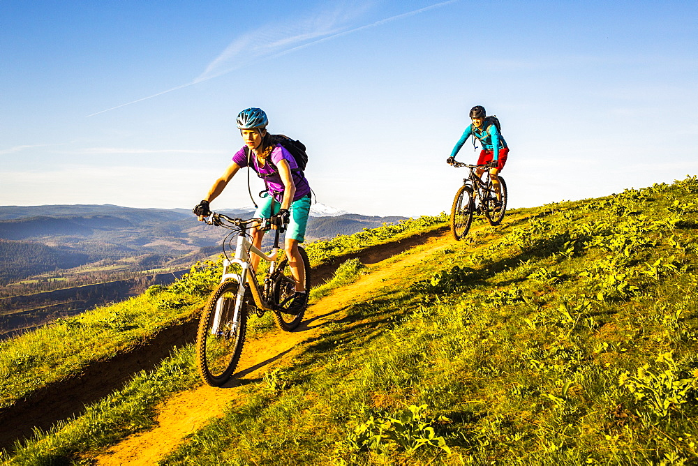 Two young women ride mountain bikes downhill on a single-track trail through green grass in early morning sunlight.