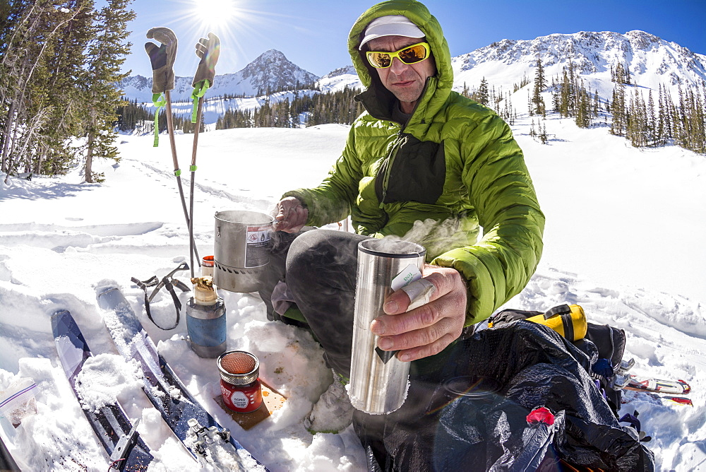 A man makes hot tea while on a backcountry ski tour below the Pfeifferhorn in Little Cottonwood Canyon, Lone Peak Wilderness, Uinta-Wasatch-Cache National Forest, Salt Lake City, Utah.