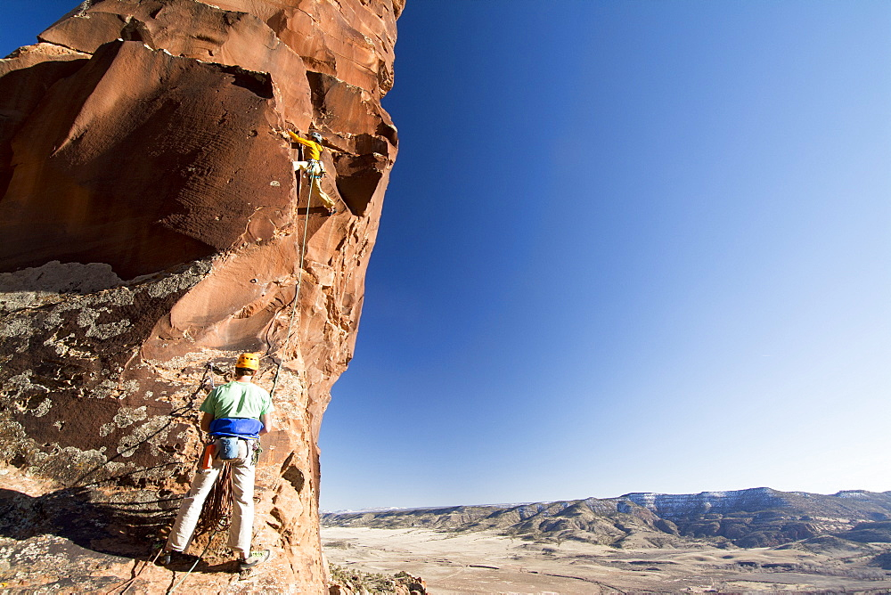 A man and woman rock  climbing a route called  Psycho Path on Psycho Tower above the Big Gypsum Valley, Naturita, Colorado.