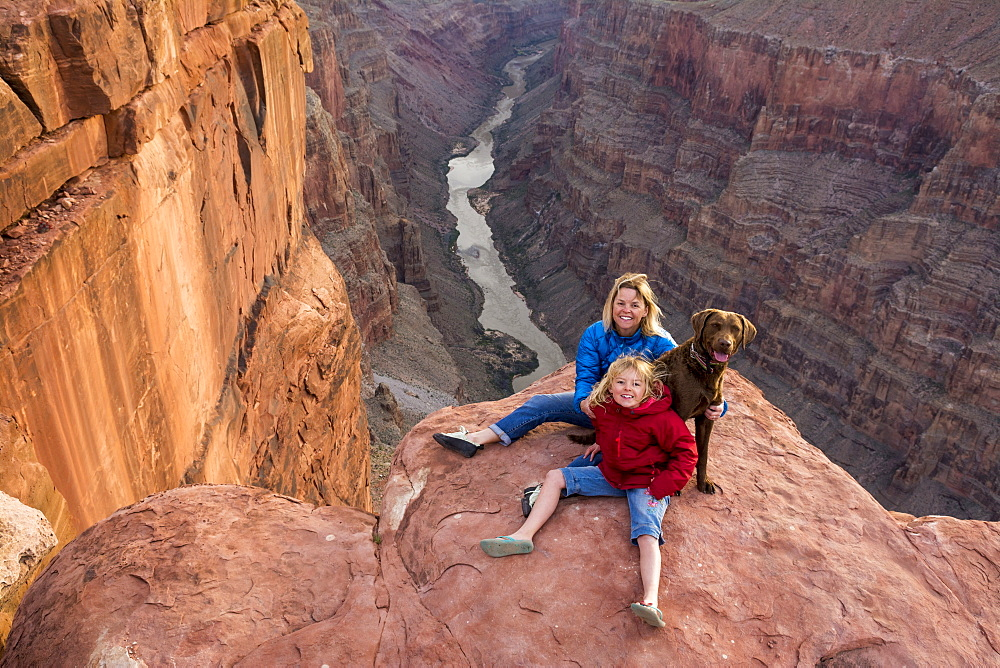 A mother and daughter and their dog sitting on the edge of Toroweap Overlook above the Colorado River, Grand Canyon National Park, Fredonia, Arizona.