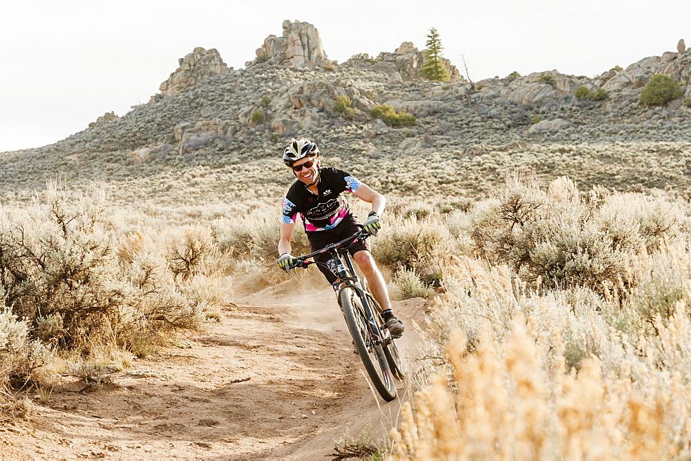 Person Mountain Biking On Trail In Desert Landscape