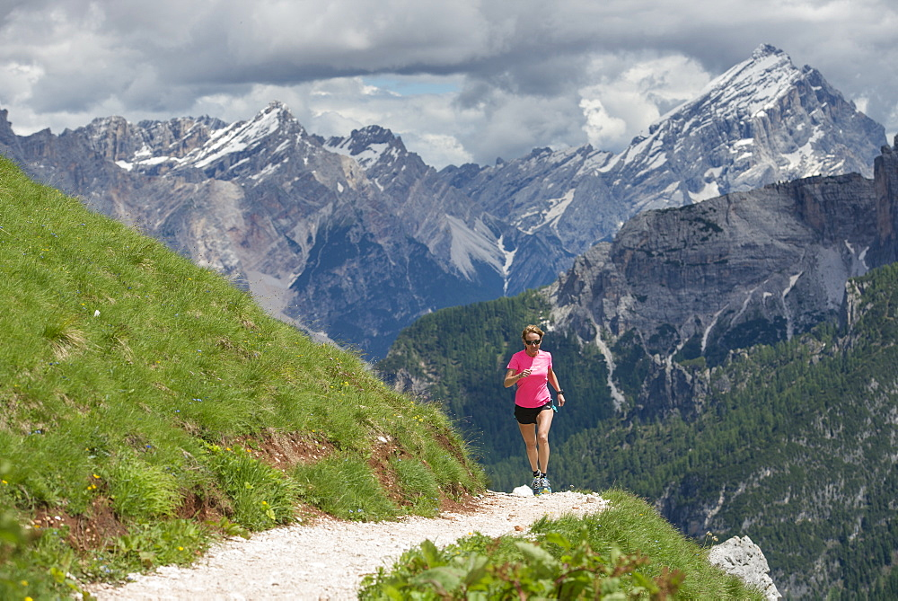 A Woman Trail Running At The Cinque Torri Area With The Croda Da Lago And Lastoi De Formin In The Background