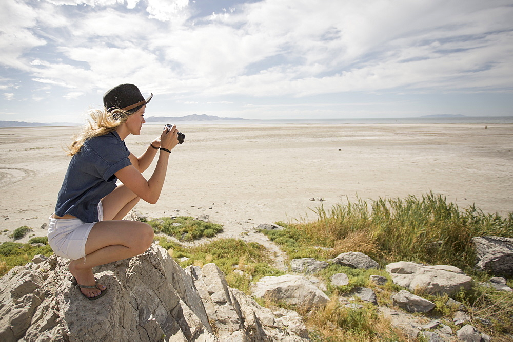 Young woman taking picture of desert in camera