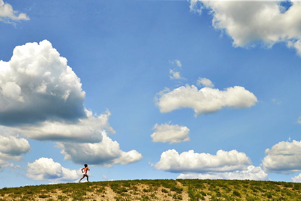 Long Exposure Of Woman Running Along The Horizon