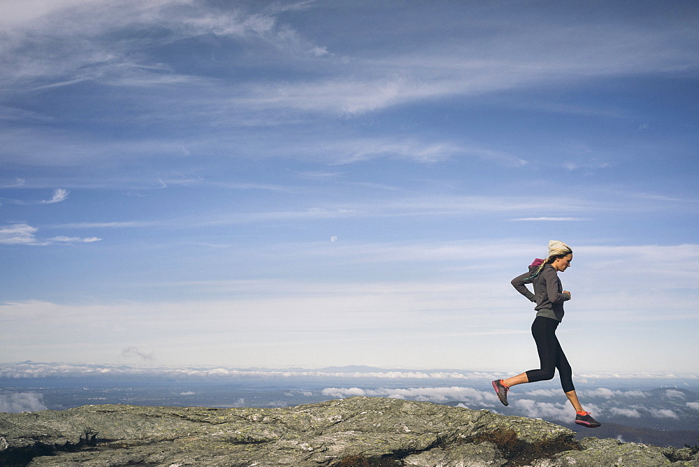 Woman Running On A Rocky Ridgeline Of Mount Mansfield, Vermont