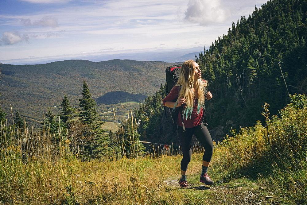 Female Hiker Hiking On Grassy Field In Mount Mansfield