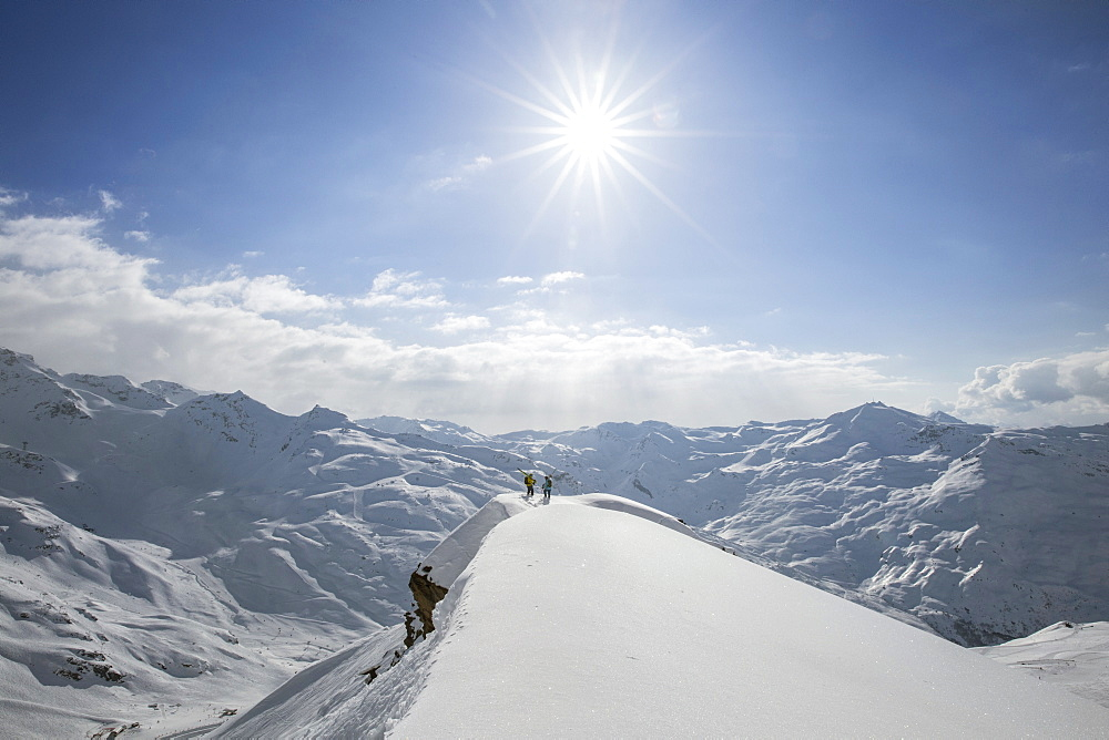 Two Skiers Seeking Out A Line On The Limit Of A Ridge