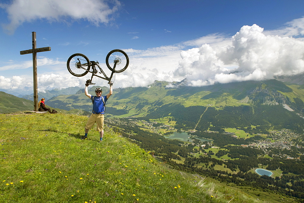 A Mountain Biker Standing On Summit Of Mountain Lifting Mountain Bike Above His Head