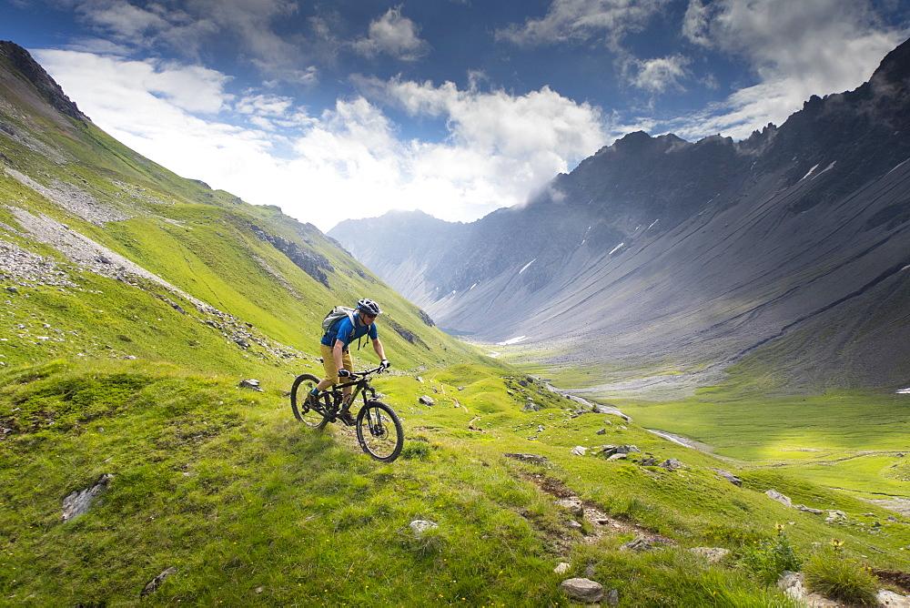 A Mountain Biker Riding Downhill In An Alpine Meadow Landscape