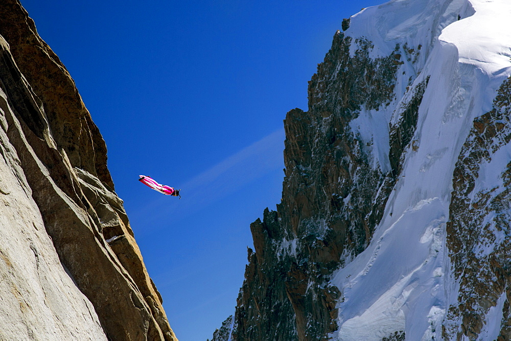 Person Flying In A Bright Red-and-white Wingsuit Between Two Mountains