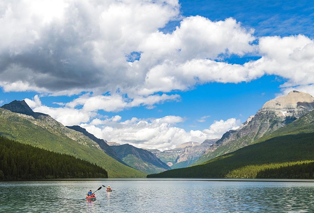 Two Kayakers Kayaking On Bowman Lake In Glacier National Park