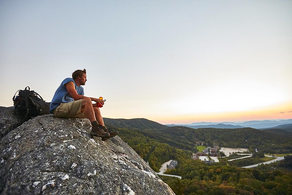 A Man Sits On A Rock Enjoying The Sunset Along The Appalachian Trail