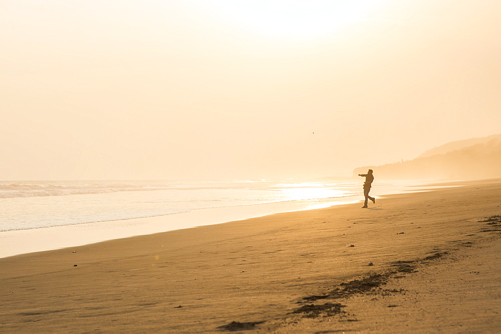 A Man Throws Beach Rocks Into The Ocean At Sunset At Popoyo Beach, Nicaragua