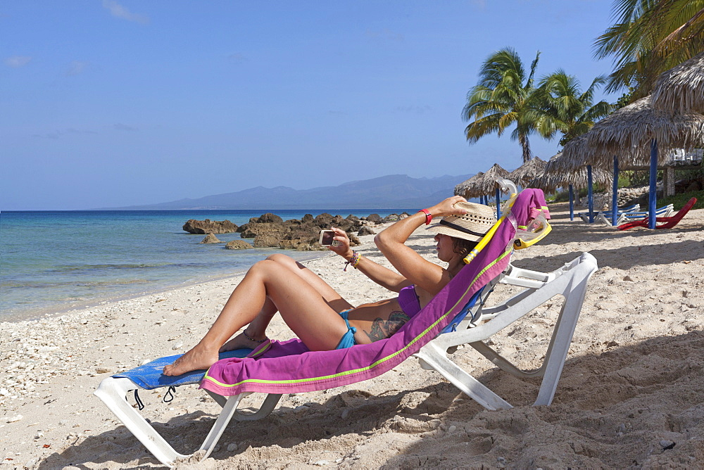 Girl Taking Picture While Sunbathing On Beach In Cuba