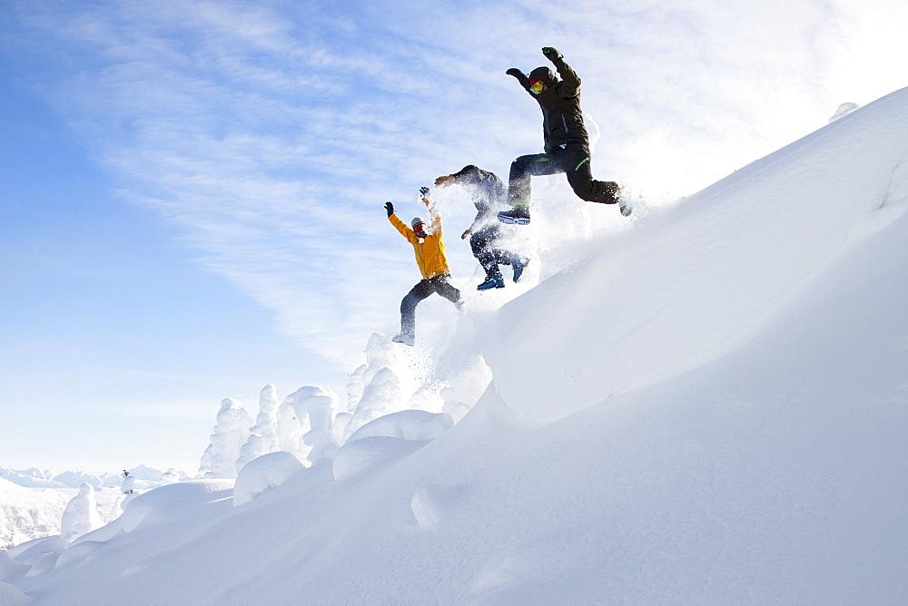 Three Men Jumping Off A Snow Cornice Near Whitefish, Montana, Usa