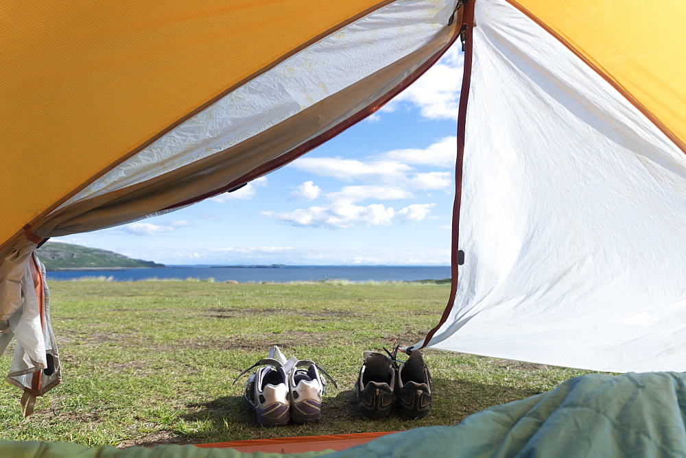 View Of Cycling Shoes From Inside The Tent On Grassy Land