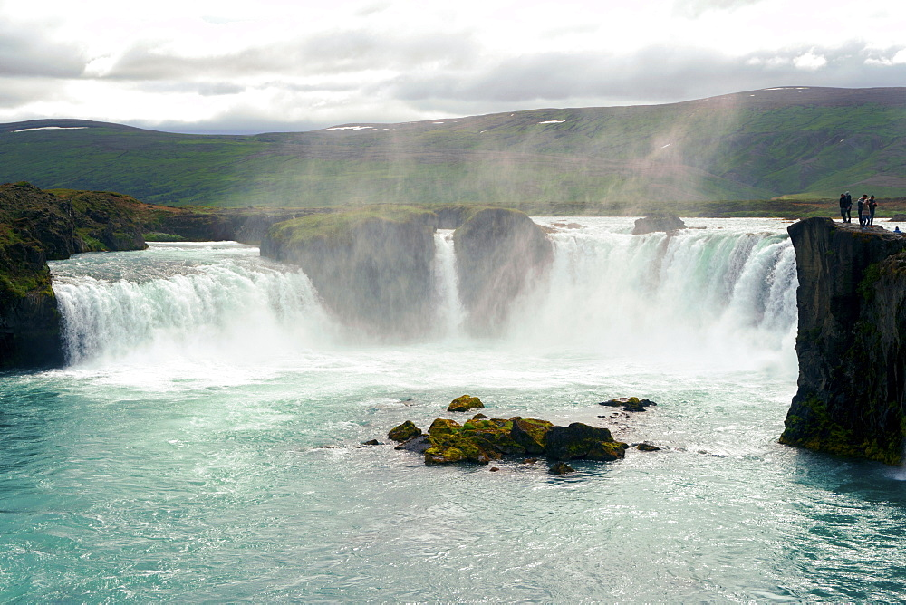 Distant View Of A People Exploring Godafoss Waterfall In Iceland