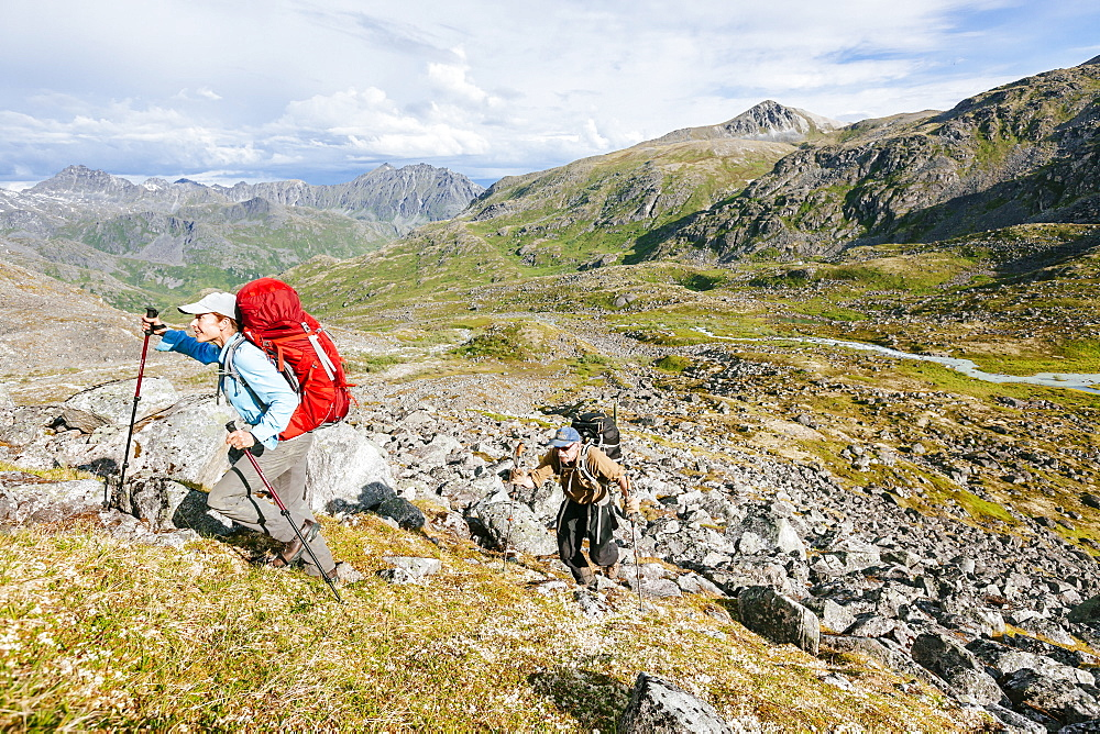 Man And Woman Hiking Up A Steep Hill In Talkeetna Range In Alaska, Usa