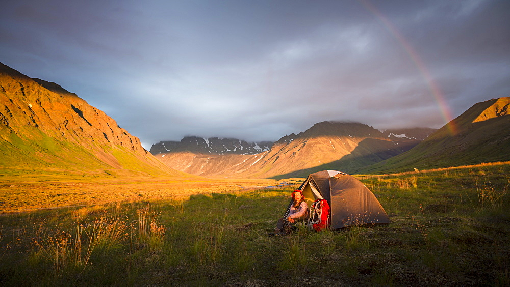 A Woman Is Sitting By Her Tent As A Rainbow Arcs Over Camp In Lake Clark National Park And Preserve