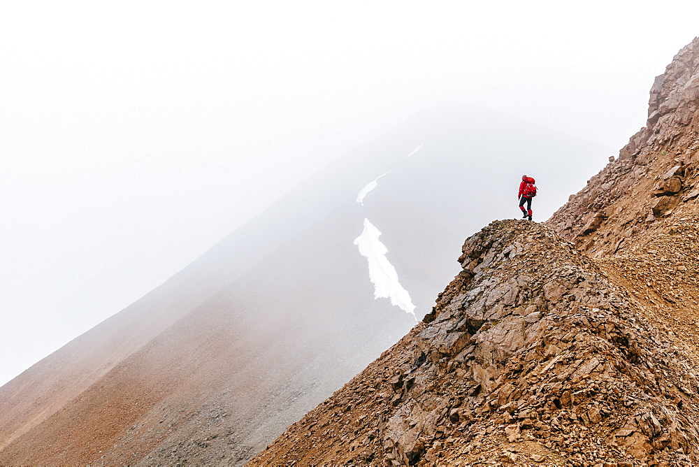 A Woman Is Hiking On A Ridge In Fog In The Delta Mountains, Alaska Range, Alaska, Usa