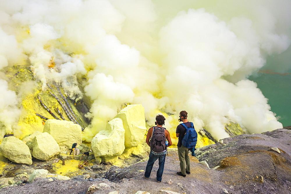 Two Men Exploring Sulfur Dioxide Smoke At Kawah Ijen, Java, Indonesia