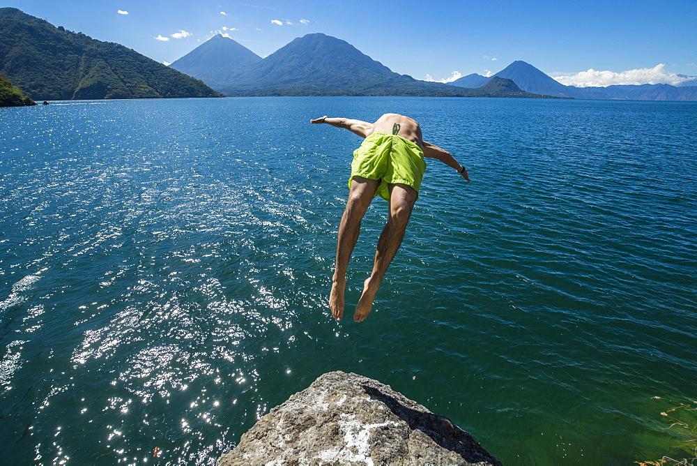 Athletic Man Backflipping In Lake Atitlan In Guatemala
