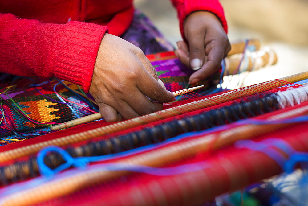 A Mayan Woman Works Carefully As She Weaves The Brightly Colored Traditional Guatemalan Huipil