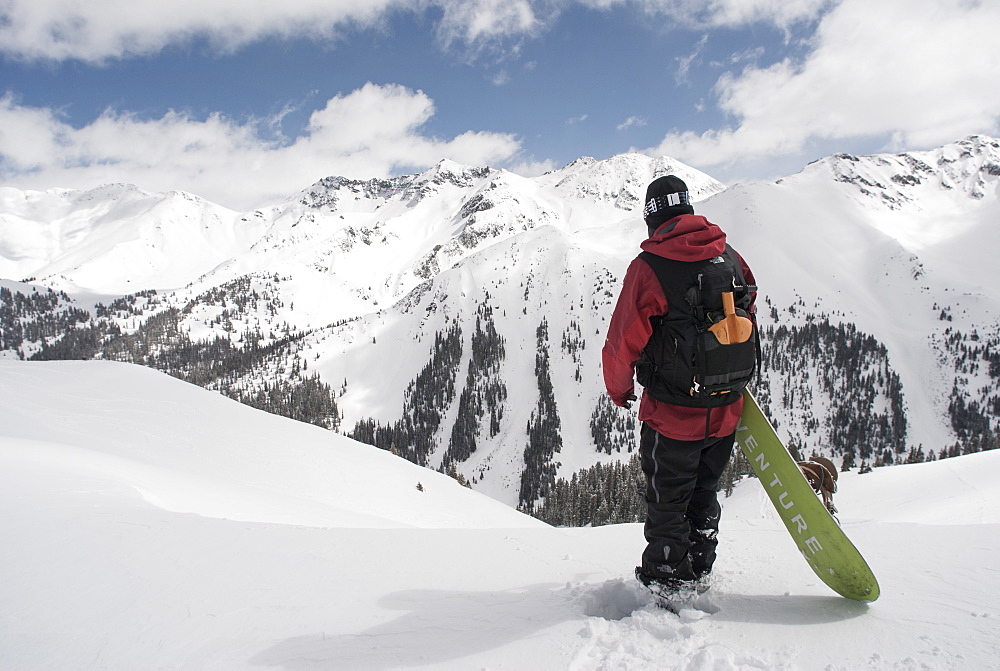 Man Standing With His Snowboard Looking Over Avalanche Paths At Silverton Mountain