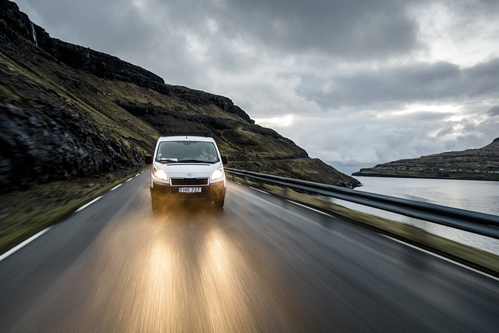 A White Car Drives Fast On A Wet Road Before Dark