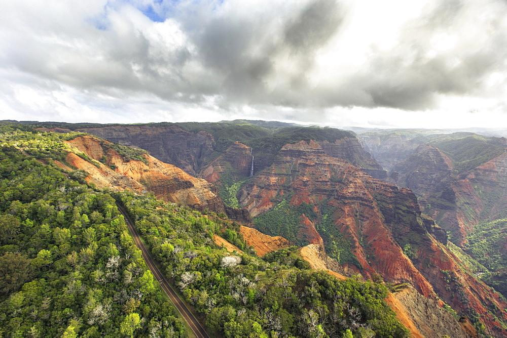 A Road Leads Past Waimea Canyon And Waipoo Falls On The Hawaiian Island Of Kauai