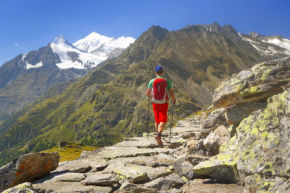 A Hiker Walking Over A Rocky Historical Trade Road With The Weisshorn Towering Above The Matterhorn Valley