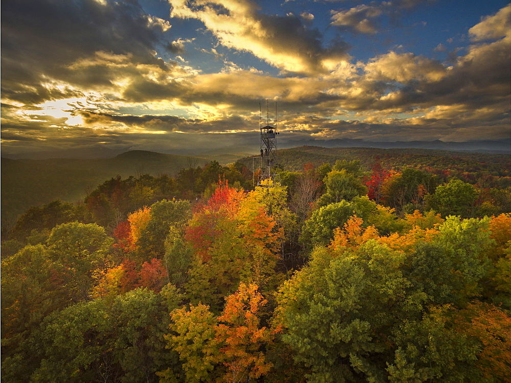 Fire Lookout Tower Surrounded By Autumn Trees With Adirondack Mountains In Background