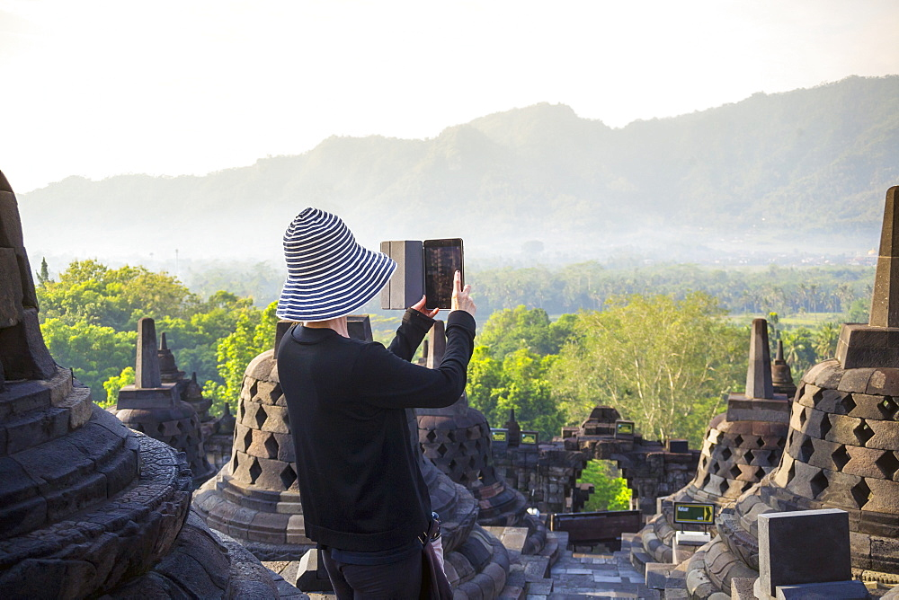 Person Taking Picture Of Borobudur Temple Using Digital Tablet In Indonesia