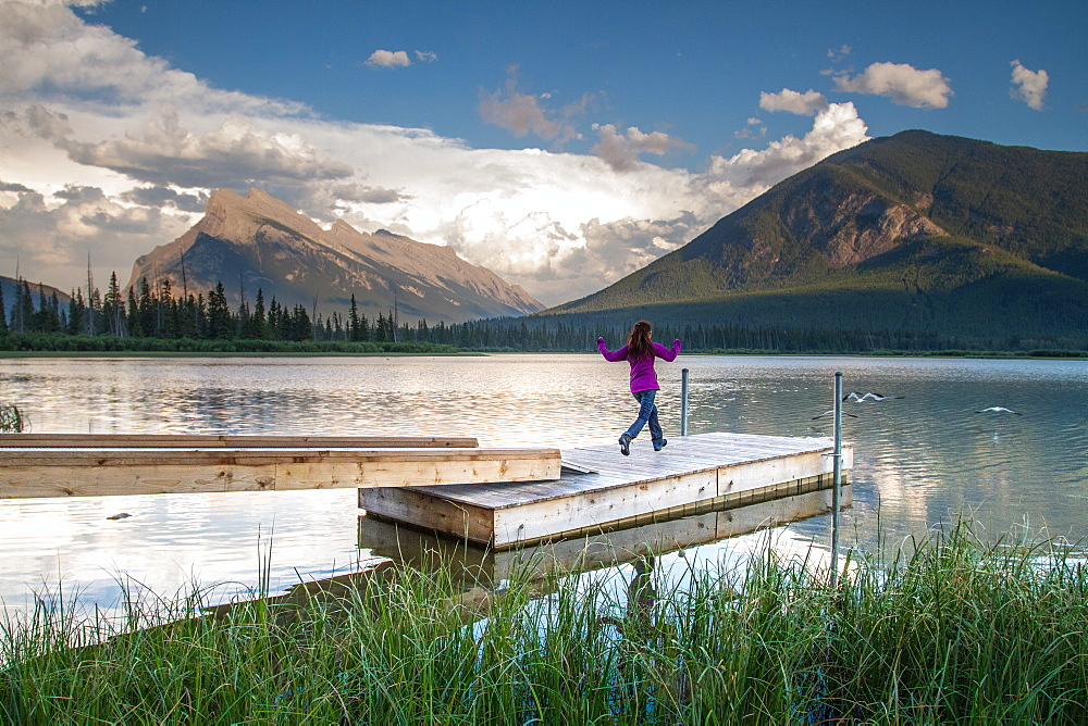 Young girl runs along wharf at mountain lake