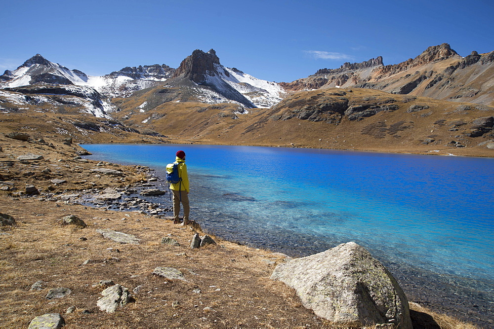 Young male stands at Ice Lake in the San Juan mountains of southern Colorado during a sunny fall afternoon
