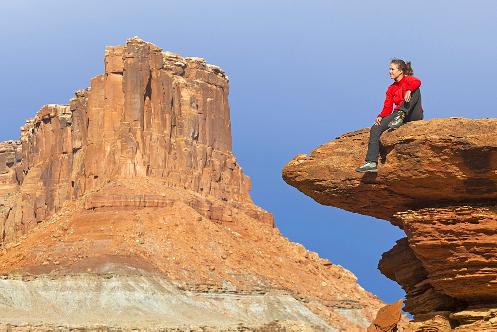 A woman sits on a bedrock terrace at Saddle Horse Bottom below tall canyon walls in Canyonlands National Park, Utah.