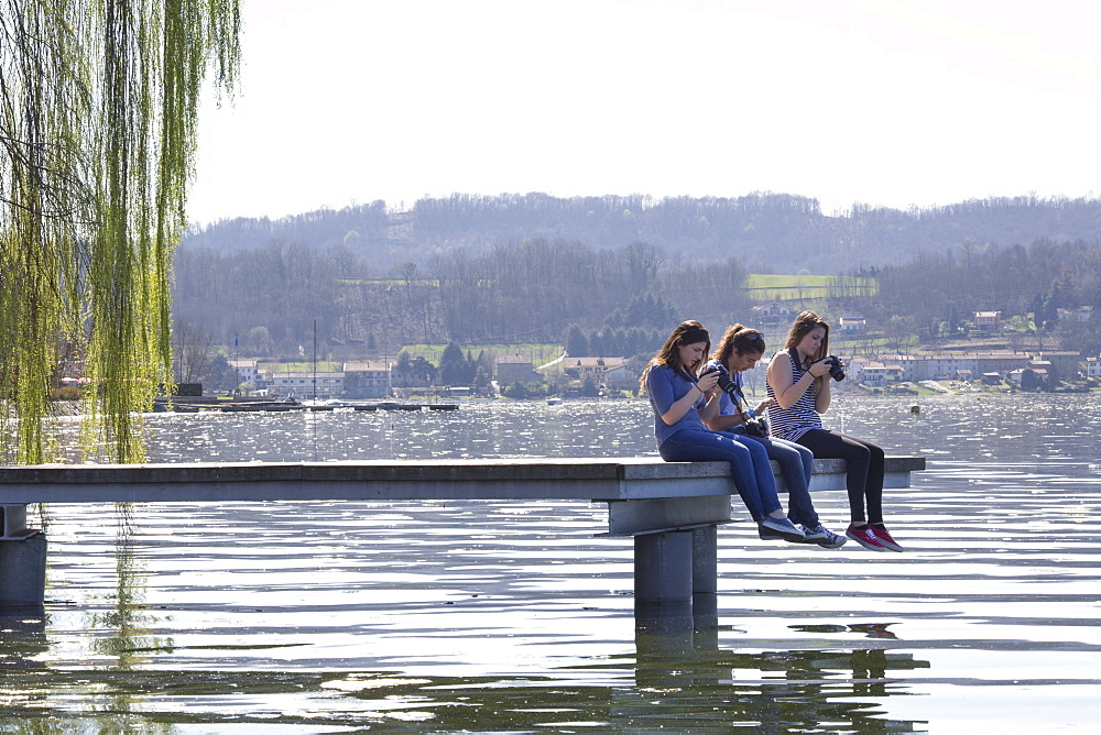 Teen girls take photos from end of pier on lake