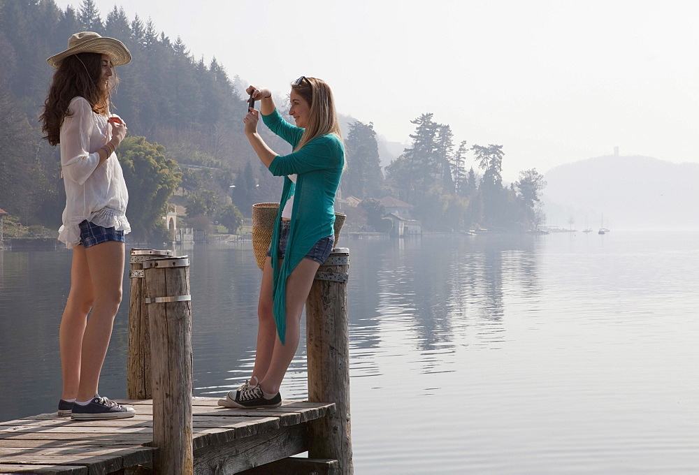 Two teen girls take photo on end of lake pier