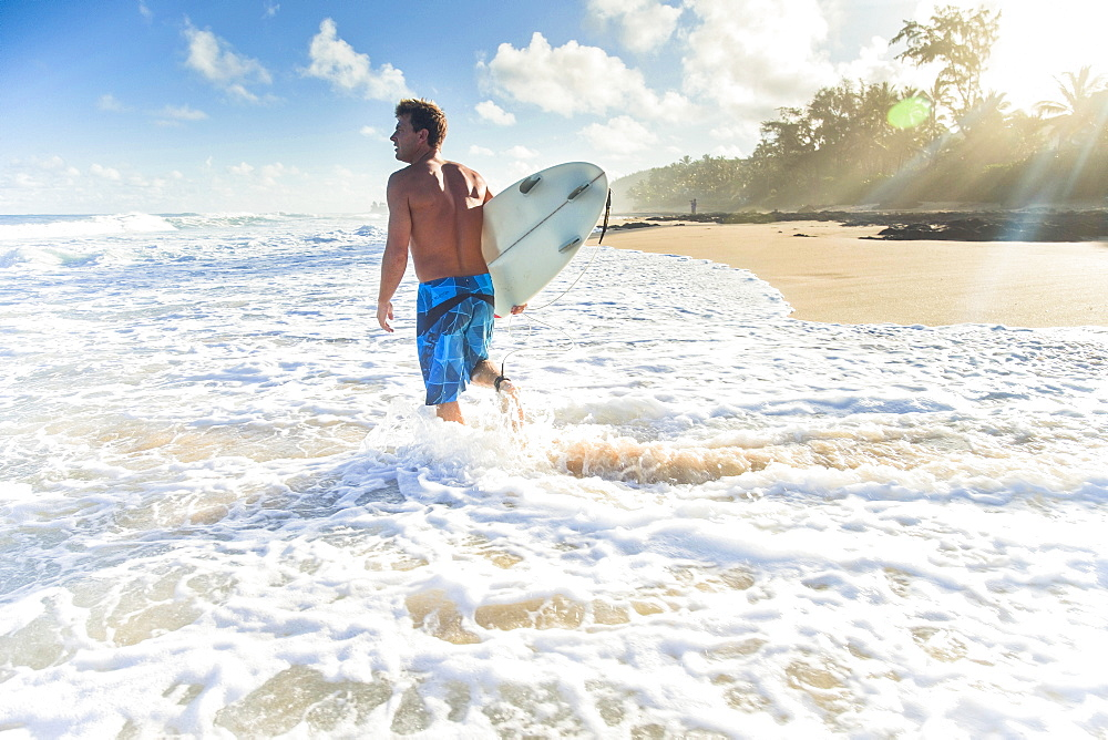 Pancho Sullivan With His Surfboard Walking On The Beach At Rocky Point On The North Shore Of Oahu, Hawaii