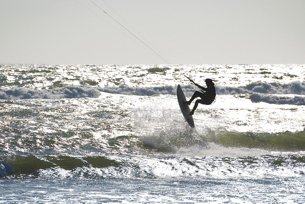 Silhouette of kite surfer enjoying a sunny winter day in Rhode Island