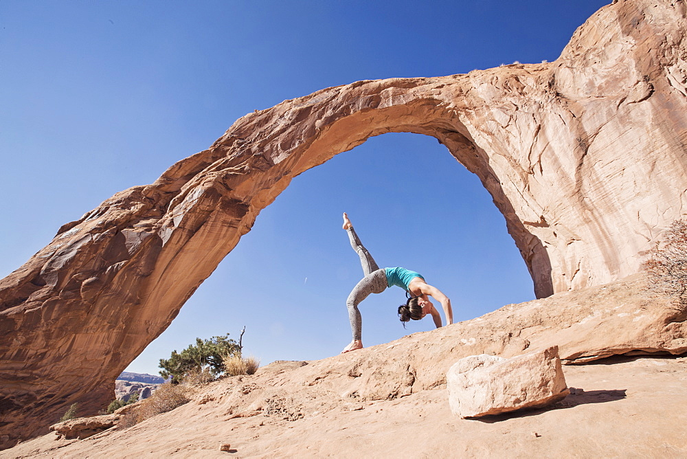 A Fit Young Woman Practices Yoga Under Corona Arch, Moab, Utah