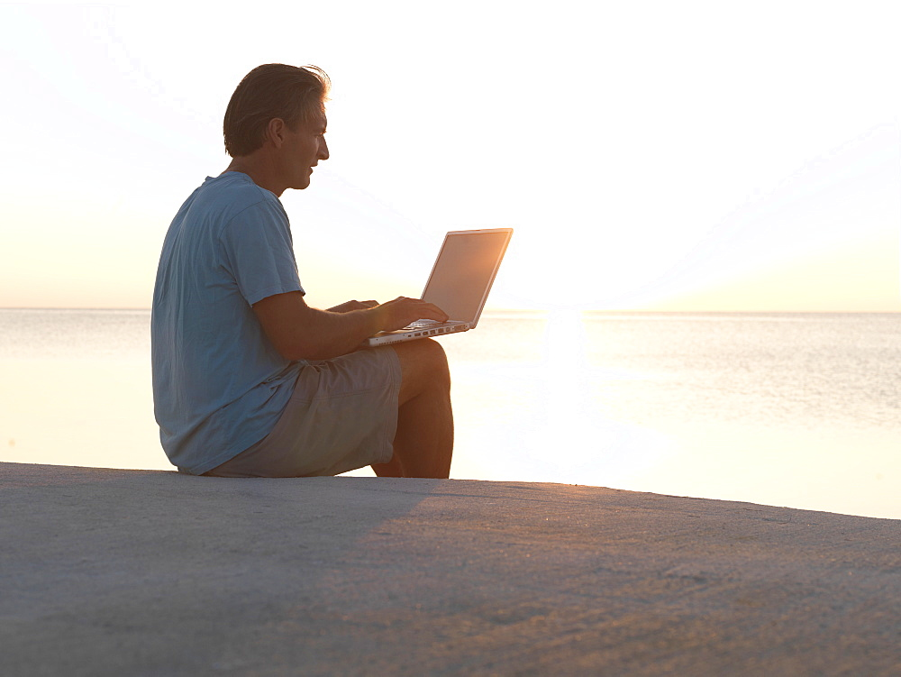 Man uses laptop computer on beach at sunset