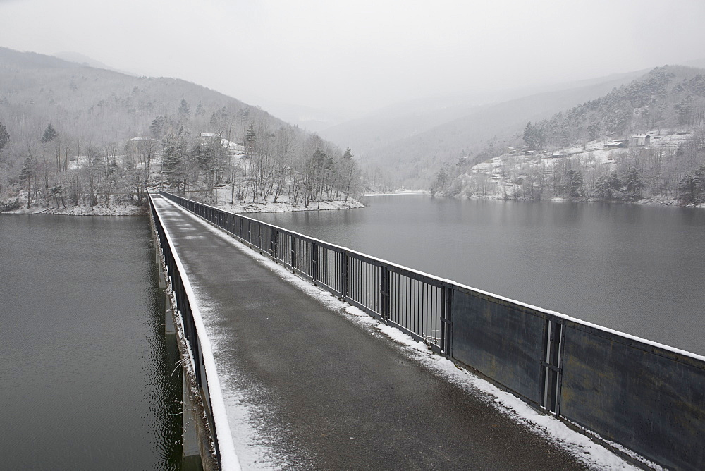 One lane bridge span mountain lake, distant hills and storm