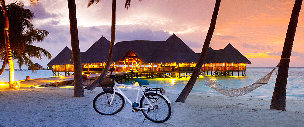 Stilt restaurant in sea behind palm trees atGiliLankanfushiisland at sunset