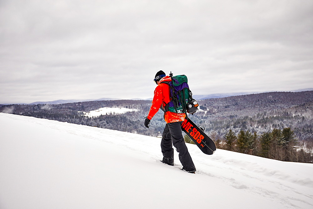 A backcountry snowboarder hiking a ridge in Vermont.