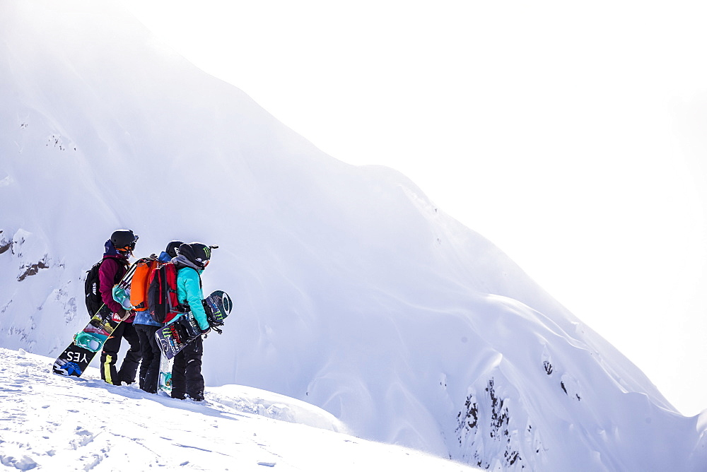 Professional snowboarders Robin Van Gyn, Helen Schettini, and Jamie Anderson, stand on a ridge and look down at a line they are about to ride on a sunny day in Haines, Alaska.